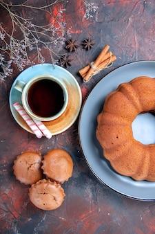 Bovenaanzicht een cake een kopje thee blauw bord cake drie smakelijke cupcakes kaneel steranijs
