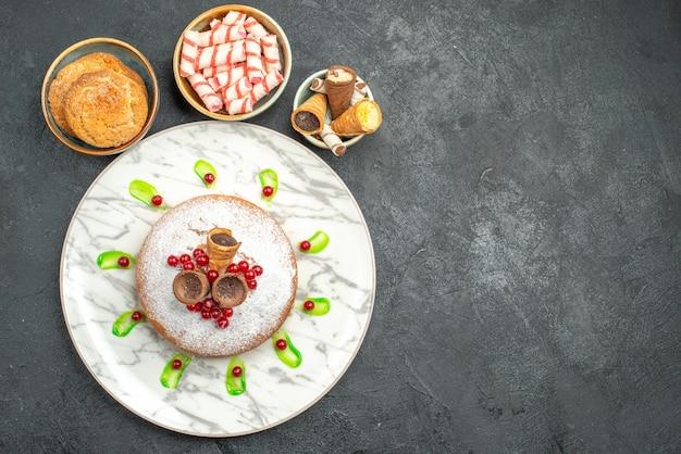 Bovenaanzicht een cake een smakelijke cake met bessen kommen koekjes kleurrijke snoepjes wafels