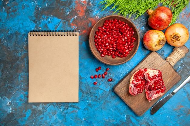 Bovenaanzicht een gesneden granaatappel en diner mes op snijplank granaatappel zaden in kom en granaatappels een notitieboekje op blauwe achtergrond