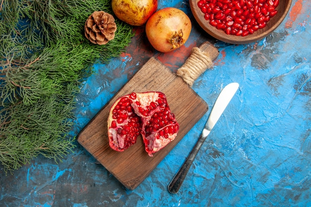 Bovenaanzicht een gesneden granaatappel op snijplank diner mes een kom granaatappelpitjes op blauwe achtergrond