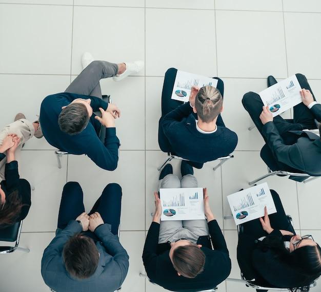 Bovenaanzicht. een groep medewerkers die naar het financiële rapport luisteren.