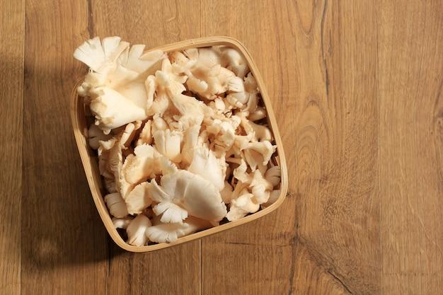 Bovenaanzicht een groep witte oesterzwammen op rieten mand op bruine houten tafel, klaar om te koken in de keuken