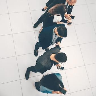 Bovenaanzicht. een groep zakenmensen die naar hun smartphoneschermen kijken. foto met een kopie van de spatie