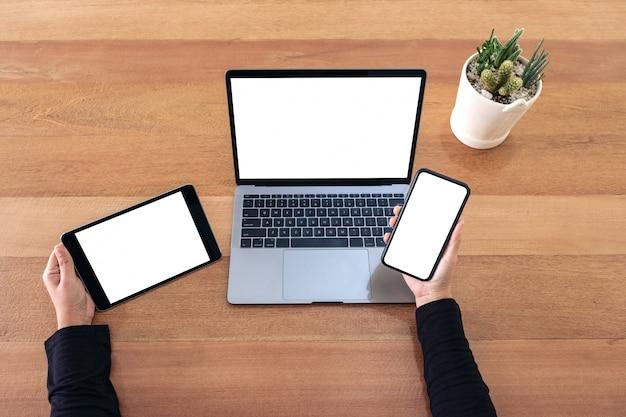 Bovenaanzicht een handen met mobiele telefoon, zwarte tablet en laptop met leeg wit scherm op houten tafel in kantoor