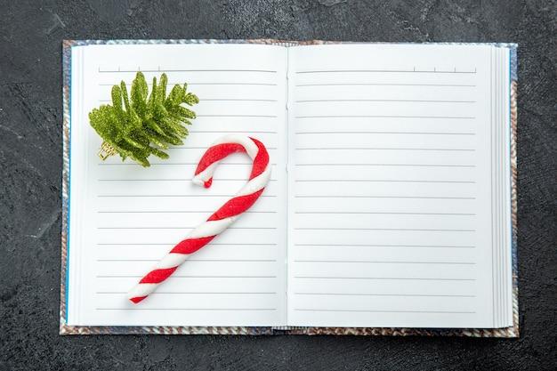 Bovenaanzicht een kerstsnoep en kerstboom speelgoed op geopend notitieboekje op donkere achtergrond