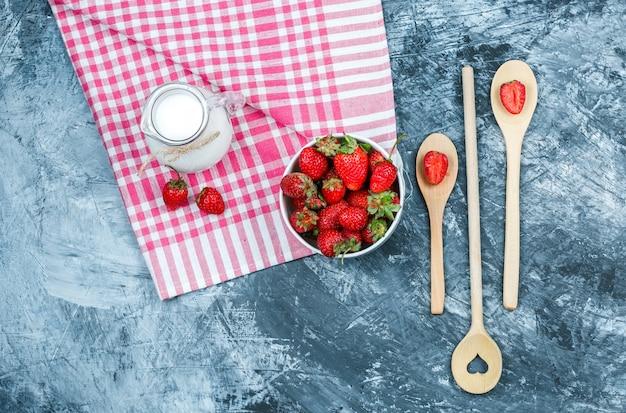 Bovenaanzicht een kom aardbeien en een kruik melk op rode geruite handdoek met houten lepels op donkerblauw marmeren oppervlak. horizontaal