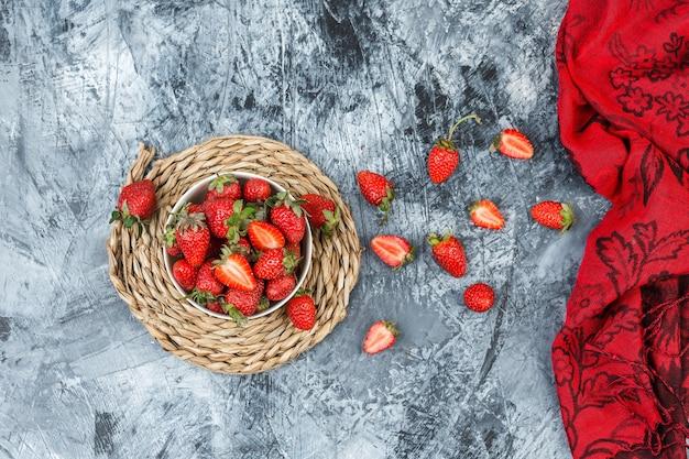 Bovenaanzicht een kom aardbeien op ronde rieten placemat met rode sjaal op donkerblauw marmeren oppervlak. horizontaal