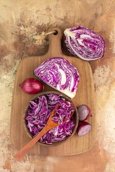 Bovenaanzicht een kom gehakte kool en wat rode uien op een houten snijplank voor de bereiding van groentesalade op een houten tafel met kopieerruimte