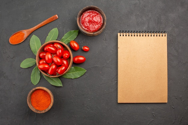 Bovenaanzicht een kom met cherrytomaatjes laurierblaadjes een houten lepel en kommen ketchup en hete peper poeder en een notitieboekje op de zwarte tafel