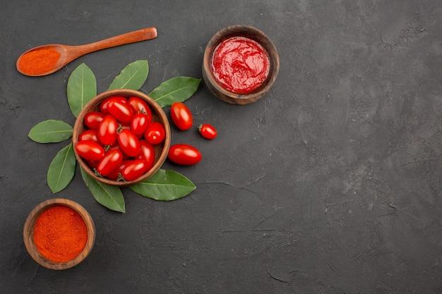 Bovenaanzicht een kom met cherrytomaatjes laurierblaadjes een houten lepel en kommen ketchup en hete peper poeder op de zwarte tafel