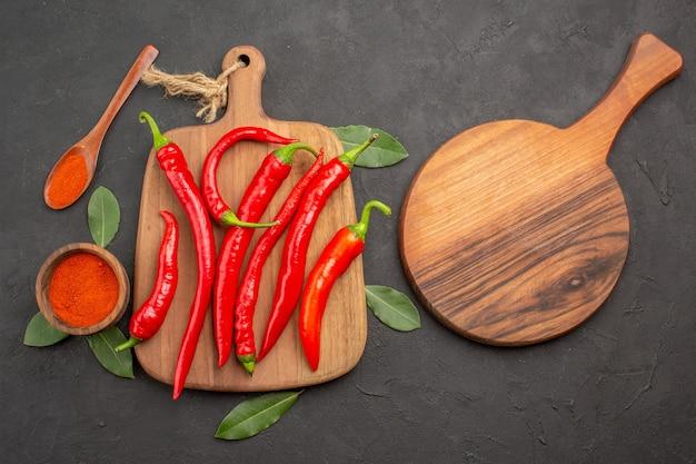 Bovenaanzicht een kom met hete peper poeder rode paprika's op de snijplank laurierblaadjes een houten lepel en een ovale snijplank op de zwarte tafel