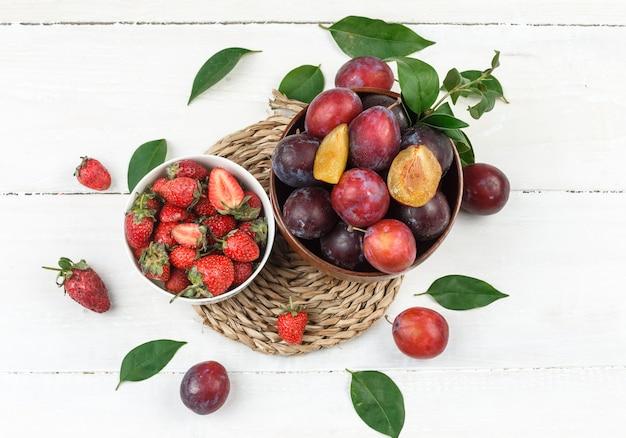 Bovenaanzicht een kom pruimen en aardbeien op rieten placemat op witte houten bord tafel. horizontaal