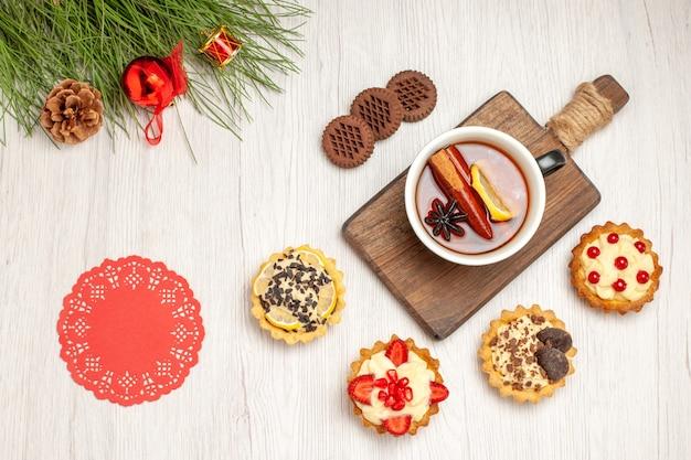 Bovenaanzicht een kopje citroen-kaneelthee op de snijplank, taartjes, koekjes en de dennenboombladeren met kerstspeelgoed en rood ovaal kanten kleedje op de witte houten grond