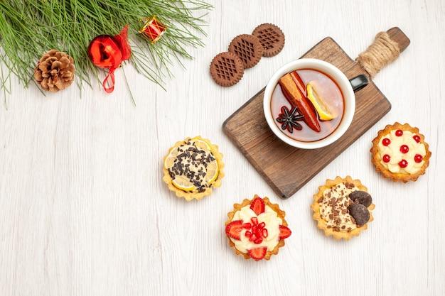 Bovenaanzicht een kopje citroen-kaneelthee op de snijplank, taartjes, koekjes en de dennenboombladeren met kerstspeelgoed op de witte houten grond