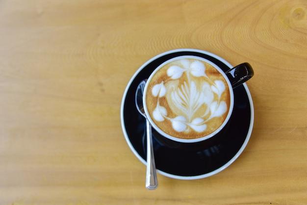 Bovenaanzicht een kopje koffie, cappuccino kunst, latte kunst, hete latte, cappuccino op houten tafel in café