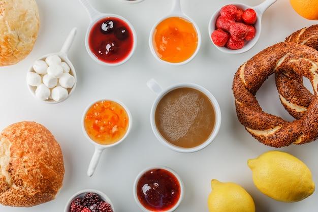 Bovenaanzicht een kopje koffie met jam, framboos, suiker, chocolade in kopjes, turkse bagel, brood, citroen op wit oppervlak
