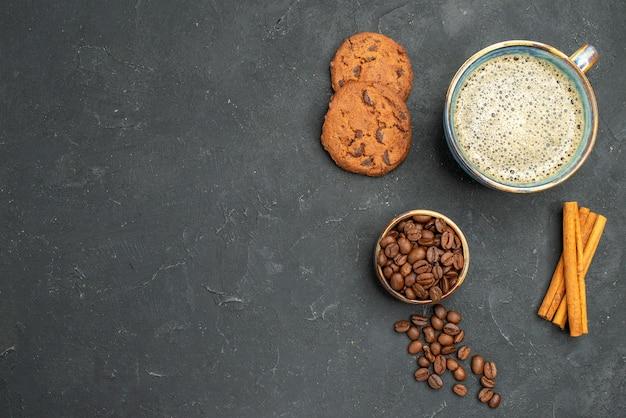 Bovenaanzicht een kopje koffiekom met koffiezaden kaneelstokjes bircuits op donkere geïsoleerde achtergrond