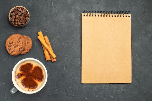 Bovenaanzicht een kopje koffiekom met koffiezaden, kaneelstokjes, koekjes en een notitieboekje op donkere geïsoleerde achtergrond