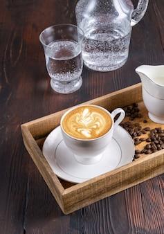 Bovenaanzicht een kopje latte art koffie, water en koffiebonen in een houten kist op een donker
