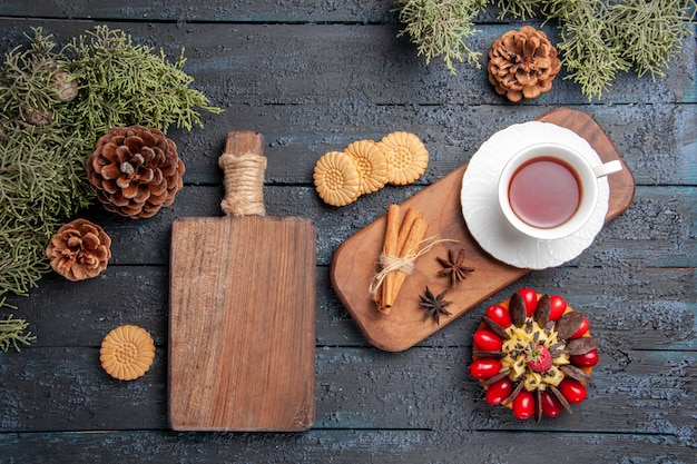 Bovenaanzicht een kopje thee anijs zaden en kaneel op houten serveerschaal koekjes dennenappels bessen cake en snijplank op donkere houten tafel