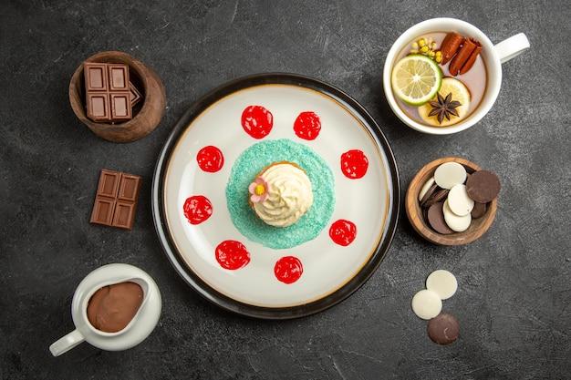 Bovenaanzicht een kopje thee bord van een smakelijke cupcake een kopje thee met kaneelstokjes en citroen en een kom chocolade en chocoladeroom op de zwarte tafel