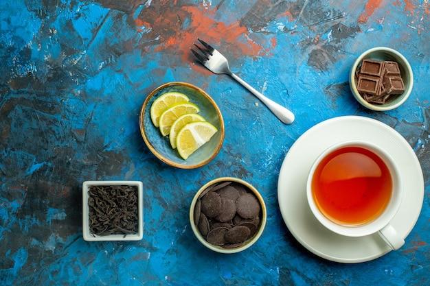 Bovenaanzicht een kopje thee chocolaatjes kemon plakjes vork op blauw rood oppervlak