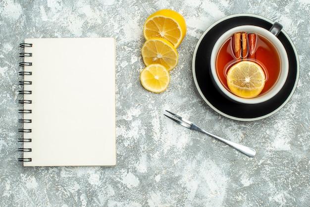 Bovenaanzicht een kopje thee citroen plakjes notebook op grijze oppervlakte vrije ruimte
