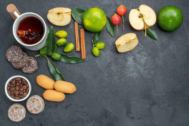 Bovenaanzicht een kopje thee citrusvruchten een kopje kruidenthee kaneelstokjes appels koekjes