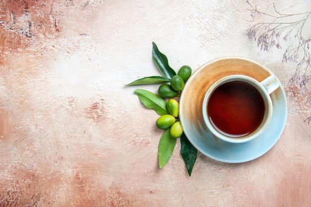 Bovenaanzicht een kopje thee citrusvruchten een kopje thee op de schotel