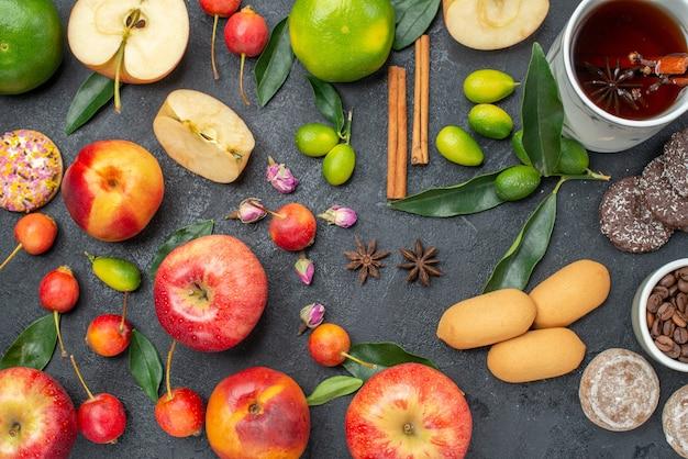 Bovenaanzicht een kopje thee een kopje kruidenthee snoepjes fruit en bessen kaneelstokjes