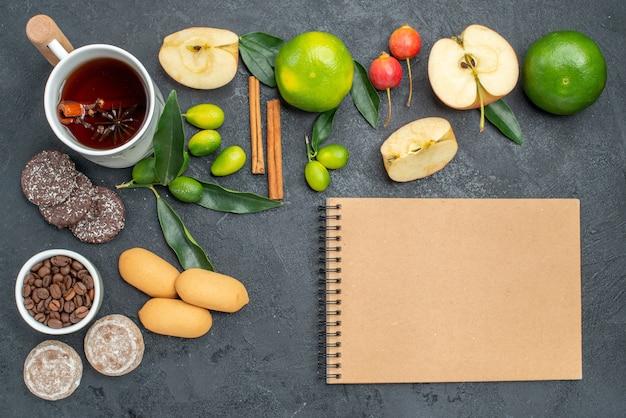 Bovenaanzicht een kopje thee een kopje thee appels bessen citrusvruchten koekjes crème notitieboekje