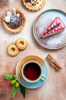 Bovenaanzicht een kopje thee een kopje thee cupcakes koekjes kaneelcake citrusvruchten
