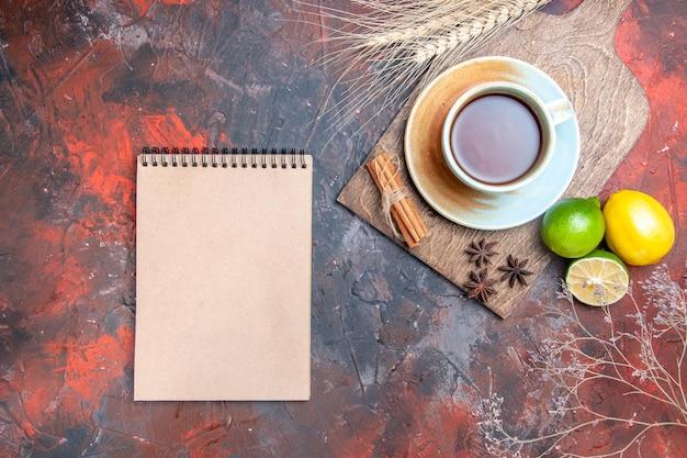 Bovenaanzicht een kopje thee een kopje thee steranijs citroen kaneel op de snijplank witte notebook