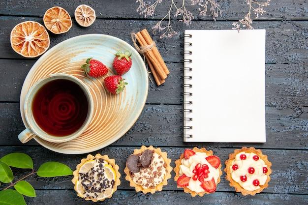 Bovenaanzicht een kopje thee en aardbeien op schotel kaneel gedroogde sinaasappeltaartjes bladeren en een notitieboekje op donkere achtergrond