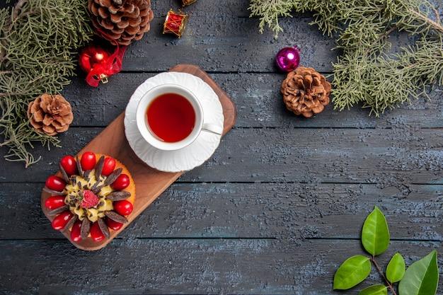 Bovenaanzicht een kopje thee en bessencake op houten serveerschaal dennenappels kerstmisspeelgoed en bladeren op donkere houten tafel