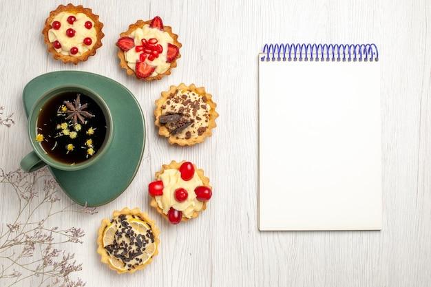 Bovenaanzicht een kopje thee en verschillende koekjes aan de linkerkant en een notitieboekje aan de rechterkant van de witte houten tafel