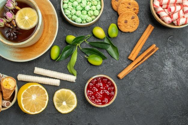 Bovenaanzicht een kopje thee koekjes een kopje thee kleurrijke snoepjes citrusvruchten kaneelstokjes