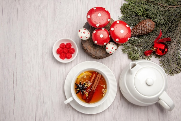 Bovenaanzicht een kopje thee kruidenthee met citroen en kaneel in de beker naast de theepot bessen en takken van de kerstboom met kegel en kerstboom speelgoed op tafel