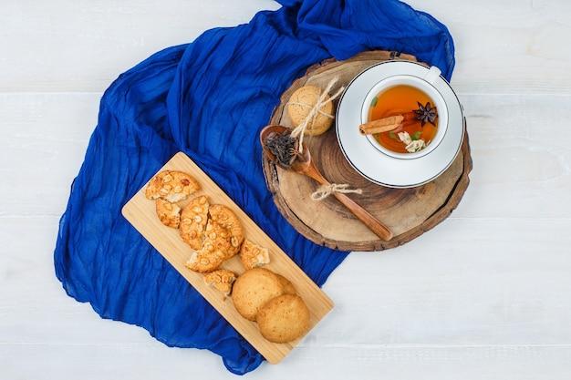 Bovenaanzicht een kopje thee, kruidnagel en koekjes op een houten bord met koekjes en kaneel op snijplanken