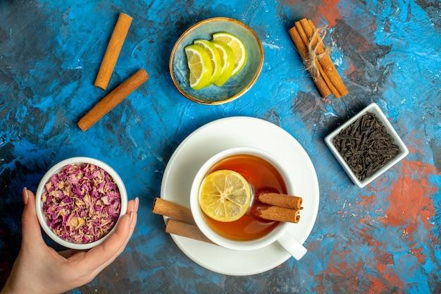 Bovenaanzicht een kopje thee met citroen en kaneelstokjes vrouw hand met gedroogde rozenblaadjes kom op blauw rood oppervlak