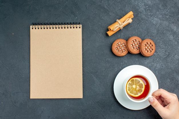Bovenaanzicht een kopje thee met citroen kaneelstokjes koekjes kladblok op donkere ondergrond