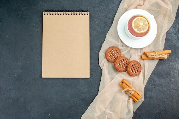 Bovenaanzicht een kopje thee met citroen-kaneelstokjes koekjes op beige sjaal kladblok op donkere oppervlakte vrije ruimte