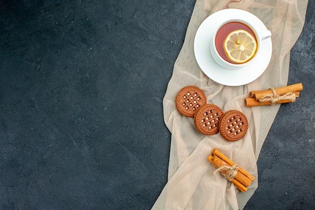 Bovenaanzicht een kopje thee met citroen kaneelstokjes koekjes op beige sjaal op donkere oppervlakte vrije ruimte