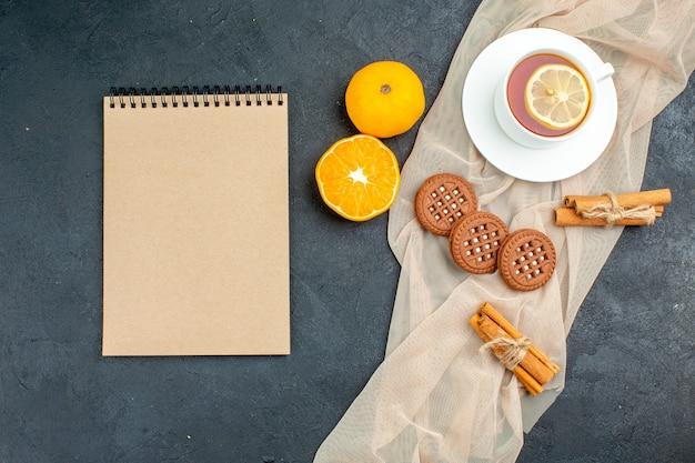 Bovenaanzicht een kopje thee met citroen kaneelstokjes koekjes op beige sjaal oranje blocnote op donkere ondergrond