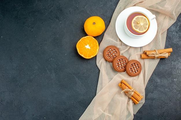 Bovenaanzicht een kopje thee met citroen kaneelstokjes koekjes op beige sjaalsinaasappel op donkere oppervlakte vrije ruimte
