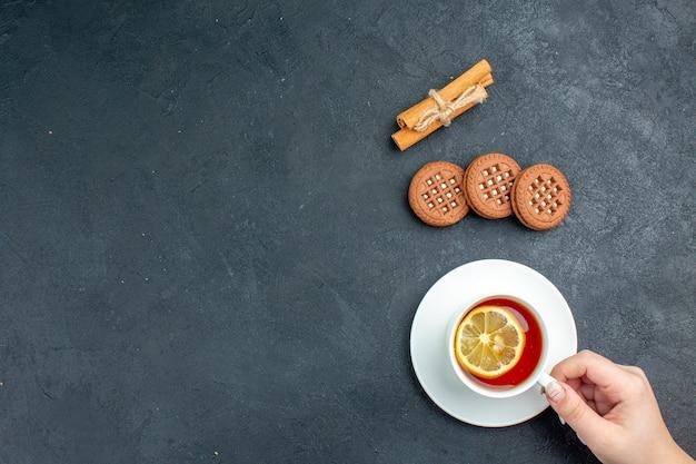 Bovenaanzicht een kopje thee met citroen kaneelstokjes koekjes op een donkere ondergrond met kopie ruimte