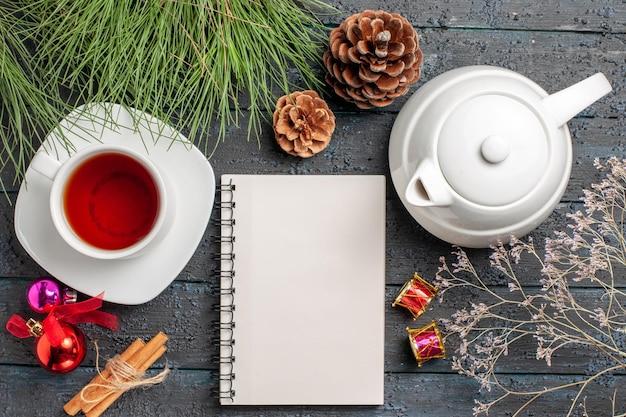 Bovenaanzicht een kopje thee witte kopje thee theepot koekjes naast de kaneelstokjes witte notebook vuren takken met kerstspeelgoed en kegels op tafel
