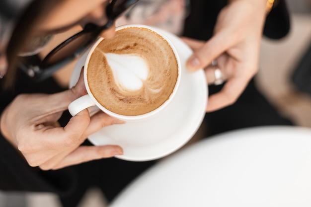 Bovenaanzicht een kopje warme cappuccino met schuim in een witte vintage beker in vrouwelijke handen. modieuze jonge vrouw in stijlvolle zonnebril geniet 's ochtends van cafeïne in een café. detailopname.