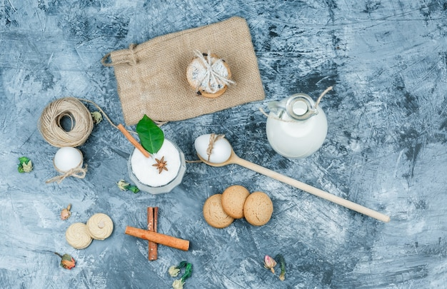 Bovenaanzicht een kruik melk en een glazen kom yoghurt met lepels, koekjes, eieren, kluwen, kaneel en een plant op donkerblauw marmeren oppervlak. horizontaal