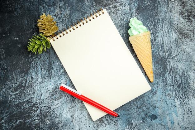 Bovenaanzicht een notebook xmas details rode pen ijs op donkere achtergrond